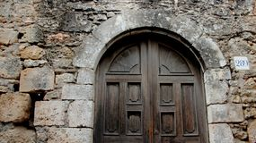 Old Wooden Door With Stone Walls. Old historic building stone walls and wooden door in Lindos Rhodes Greece stock image
