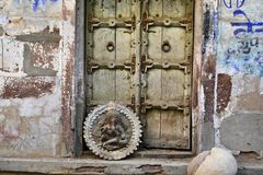 Old wooden door to aged ancient building symbol with image of Ganesha god. Old wooden door to aged ancient building. Rounded Hindu symbol with image of Ganesha royalty free stock image