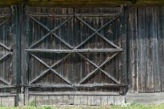 Old wooden door to the barn, gray old wooden boards. A large door to the barn made of wood. Old boards turned gray. Elements of old rural buildings royalty free stock images