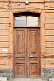 Old wooden door to house with brick wall. Entrance door to old h. Old wooden door to house with brick wall. Front of old building. Entrance door to old house Stock Photography