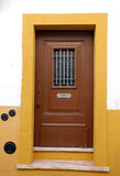 Old wooden door in white and yellow house Stock Photography
