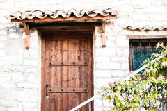 Architectural details of the town of Berat. Old wooden door and a window on a facade of the historical building in Berat Royalty Free Stock Photo