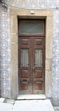 Old wooden door with window on the wall with ceramic tile Royalty Free Stock Photos