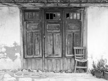 Old wooden doors in Crete, Greece. Old broken wooden doors and a chair next to old building in Crete, Greece Royalty Free Stock Image