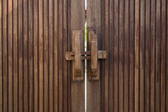 Old wooden doors locked with wooden crossbar. Old wooden doors locked with simple wooden crossbar Royalty Free Stock Photos