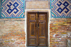 Old wooden double doors with mosaic on the walls, Registan squar Royalty Free Stock Photography