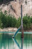 Electric pillar sticking out of water. Old wooden electric pillar drowned in the pond with bright blue water Stock Photos