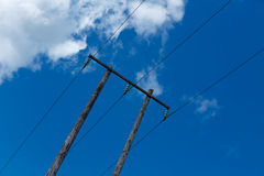 Old wooden electric post against blue sky and clouds Royalty Free Stock Photo