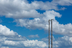 Old wooden electric post against blue sky and clouds Stock Photo