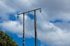Old wooden electric post against blue sky and clouds Royalty Free Stock Images