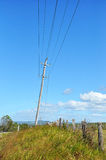 Old wooden electricity post beside the street in the countryside Royalty Free Stock Photo
