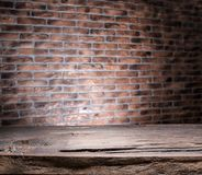 Old wooden empty table and brick wall. In the background royalty free stock images