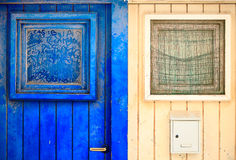 Old wooden entrance door. Old wooden blue and beige entrance door with windows Royalty Free Stock Images