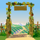 Old wooden farm gate with signboard, grapes and Mediterranean la Stock Photo