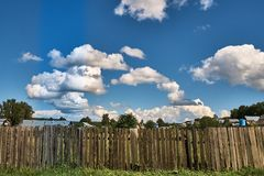 Old wooden fence on a background of clouds. Old wooden fence against the background of clouds in summer Stock Photography