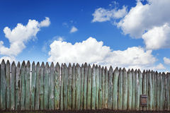 Old wooden fence against blue sky with clouds. Background Stock Photo