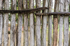 Old wooden fence. Aged round wooden fence that can see through in between each stake Stock Images