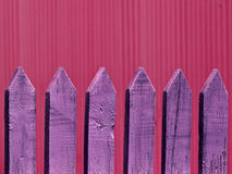 Old wooden fence, background. Old wooden fence as a background, in purple color, against red background Stock Images