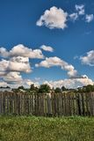 Old wooden fence on a background of clouds. Old wooden fence against the background of clouds in summer Stock Photos