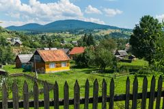 Old wooden fence on the background of a rural mountain village with pretty little houses. For your design Royalty Free Stock Image