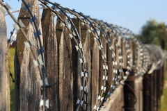Old wooden fence with barbed wire perspective Stock Photo