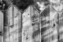Old wooden fence with barbed wire on top - monochrome. Old wooden fence with barbed wire on top - black and white artistic image Stock Photo