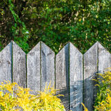 Old wooden fence with barbed wire on top. Square image Stock Photography