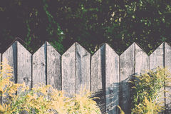 Old wooden fence with barbed wire on top. Vintage. Royalty Free Stock Image