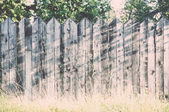 Old wooden fence with barbed wire on top. Vintage. Royalty Free Stock Photo