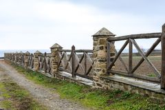 Old wooden fence with brick columns royalty free stock photography