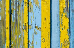 Old wooden fence with cracked paint. Old wooden fence with cracked yellow and blue paint, background royalty free stock photos