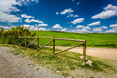 Old wooden fence, dirt road and green field Stock Photo