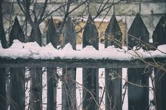 Old wooden fence of gray colour. Behind the fence wall of the large brick Royalty Free Stock Image