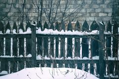 Old wooden fence of gray colour. Behind the fence wall of the large brick Stock Photography