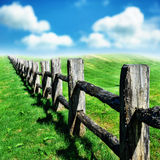 Old wooden fence at green field Royalty Free Stock Images