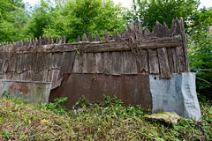 Old wooden fence. With iron sheets on the background of grass and trees Stock Photos