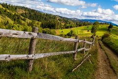Old wooden fence near the mountain road in the Carpathians Stock Photo