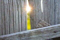 Old wooden fence and a ray of sun in a crack Stock Photo