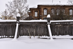 Old wooden fence of a residential house, snowbound Royalty Free Stock Photo