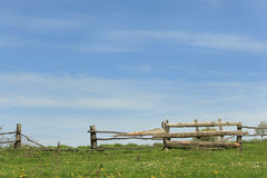 Old Wooden Fence. Old rickety wooden fence in ukrainian village with blue sky and green blooming field background stock photo