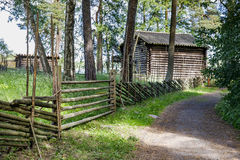 Old wooden fence and a road. To a farmhouse Stock Photos
