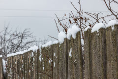 Old wooden fence with snow. Rickety fence after a snowfall Stock Photo