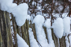 Old wooden fence with snow. Rickety fence after a snowfall Stock Images