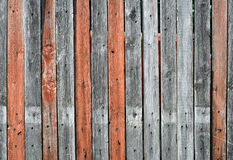 Old wooden fence texture. Close-up view of an old wooden fence with gray and orange mixed planking Royalty Free Stock Photography