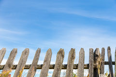 Old wooden fence. Top of old wooden fence and sky at the backgound Stock Photo