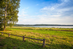 Old wooden fence  and trees on the lake coast. Russian landscape Stock Photo