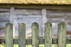 Old wooden fence, wooden wall of barn on background, copy space. Life in the village, Western Ukraine. Old wooden fence, wooden wall of barn on background, copy Royalty Free Stock Images