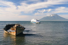 Old wooden ferry in front of a volcano, Indonesia. A sunset on Lembata island in Solor archipelago, East Indonesia with the smoking cone of IIi Api (1463 m) Stock Photos