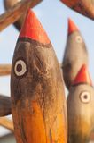 Old wooden bird birds sculpture. Old weathered wooden bird birds decorative sculpture with painted faces outdoors on a wooden structure Royalty Free Stock Photography