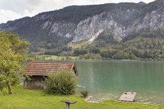 Old wooden fisherman shed on the shore of mountain lake Royalty Free Stock Images